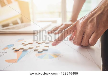 Asian business woman hands on a wooden office desk pick puzzle. Business solutions success and strategy concept. Businessman hand connecting jigsaw puzzle.Close up photo with selective focus.