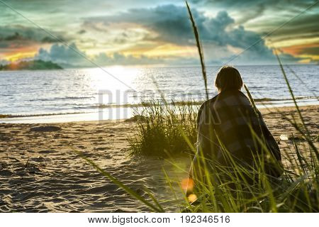 Silhouette of senior woman sitting alone in beach in front of the sea