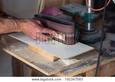 Close up of Male Carpenter's Hand using electric sander tool in his workshop