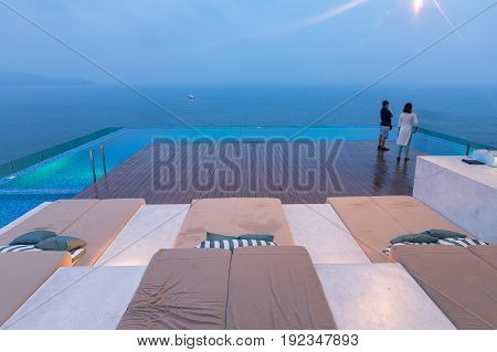 DA NANG VIETNAM - March 13 2017. Young couple on the pool terrace. Turquoise pool on the hotel roof in Vietnam. Da Nang