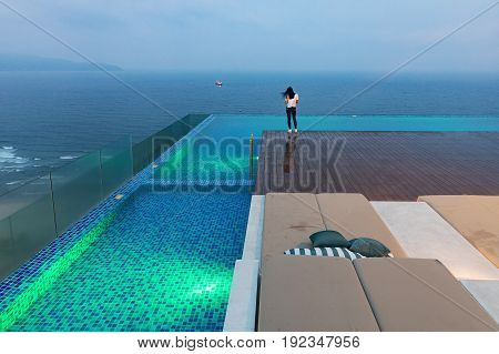 DA NANG, VIETNAM - March 13, 2017. A girl in jeans and a white shirt on a pool terrace. Turquoise pool on the hotel roof in Vietnam. Da Nang