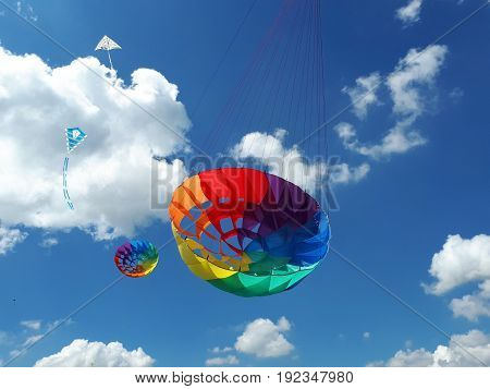 Kites Flying In A Blue Sky. Kites Of Various Shapes