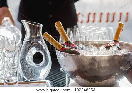 Three wine bottles chill in ice bucket on a buffet table among glasses waiter in the background