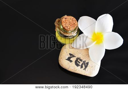 Spa decoration with massage oil,frangipani flower and zen stone on a black background.Spa concept.Selective focus.
