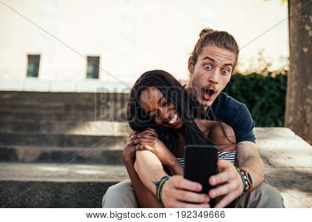 Happy couple making funny selfie together outdoors.