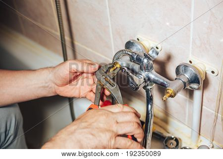 Man repair and fixing leaky faucet in bathroom