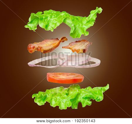Fresh sandwich in salad leaves with flying ingredients isolated on dark background. concept