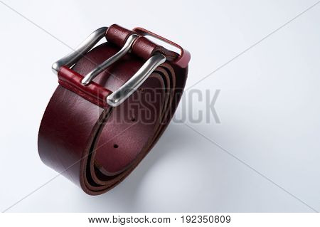 Stylish brown leather belt with a buckle isolated on white background.