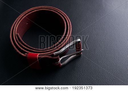 Stylish brown leather belt with a buckle on black textured leather background