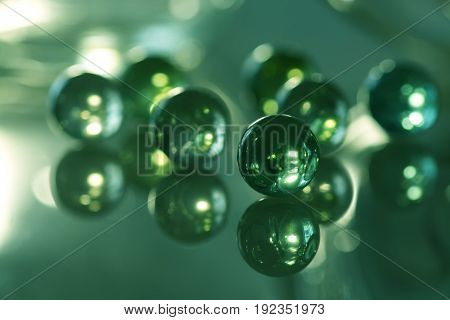 Glass balls on a glass table with a reflection of green. Seven glass balls.