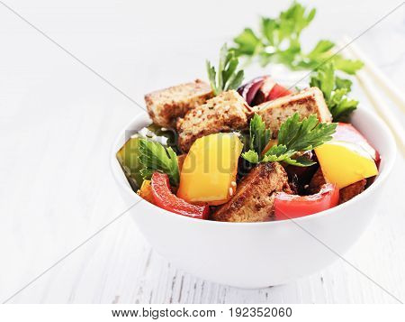 Tofu salad with pepperoni on white wooden background.