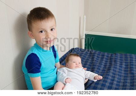 Brother with little sister smiling boy holding newborn sister