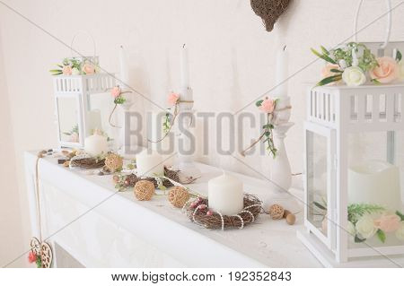 Lifestyle with candles in interior. home decor. country house decor in details. lamps decorated with white pink flowers. decorative fireplace for lush life