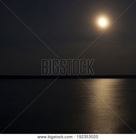Full moon rising with clouds over Dore Lake Saskatchewan
