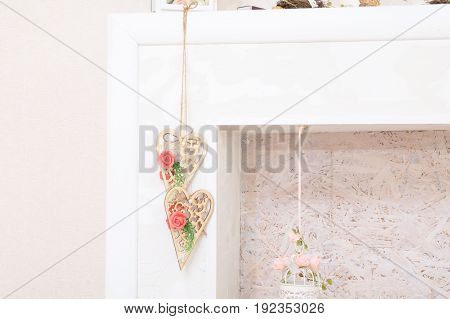 Lifestyle with wooden hearts with white and pink flowers in fireplace for lush interior. home decor. country house decor in details