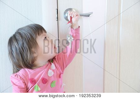 Child playing with keys forgotten by parents in door keyhole. Children safety and home safety concept.