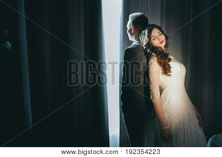 The bride and groom on the window background