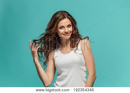 The young woman's portrait with happy emotions on studio background