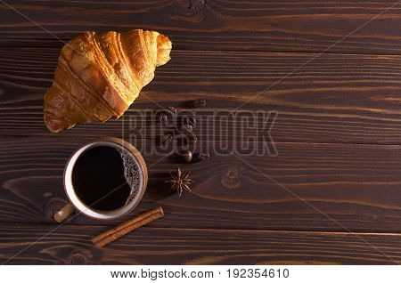 Cup of hot coffee and croissant for breakfast on dark wooden table top view. Lower light. Space for text