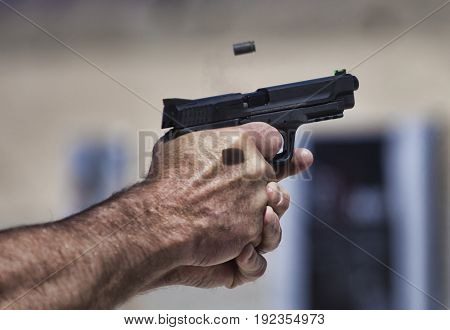 Empty brass flying from a handgun on a shooting range