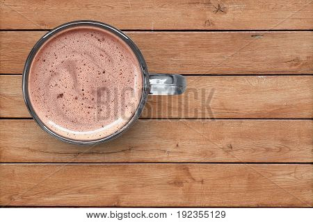 Cocoa in a glass cup on a wooden background