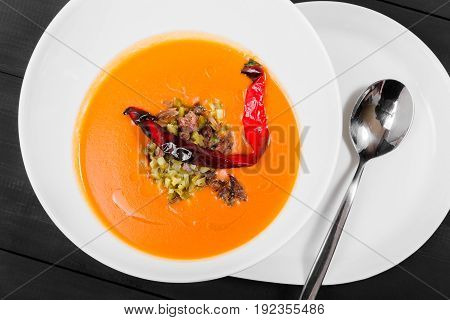 Tomato soup red pepper soup sauce with olive oil meat and pickles in bowl on black wooden background healthy food. Top view