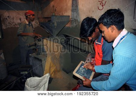 KOLKATA, JANUARY 20, 2007: A young boy is teaching a factory labour to understand the alphabets on January 20, 2007 in a rural area near Kolkata, India.