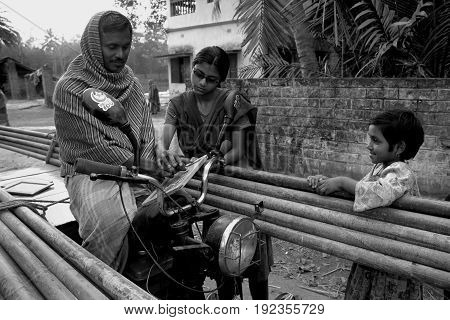 KOLKATA, JANUARY 20, 2007: A young girl is teaching an adult man to understand the alphabets on January 20, 2007 in a rural area near Kolkata, India.