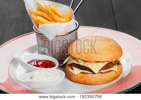 Cheeseburger hamburger with french fries ketchup mayonnaise fresh vegetables and cheese on plate on dark wooden background. American fast food