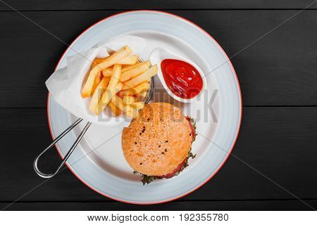 Burger hamburger with french fries ketchup mayonnaise fresh vegetables and cheese on plate on dark wooden background. American fast food. Top view