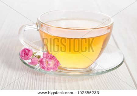 Glass cup of tea with rose on white wooden table