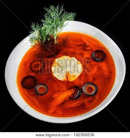 Soup with meat olives herbs and lemon in bowl isolated on black background homemade food. Traditional Russian soup - solyanka. Top view