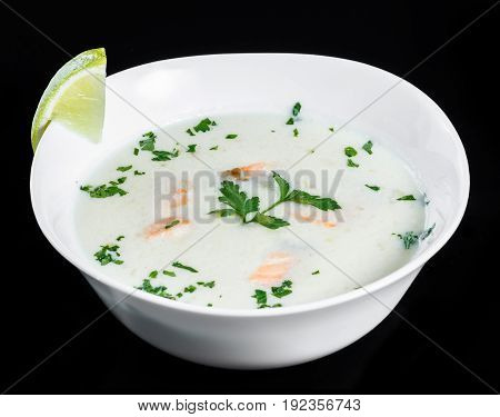 Fish soup with salmon and shrimps parsley and lemon in bowl isolated on black background healthy food. Top view