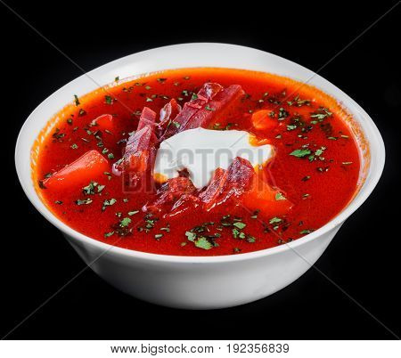 Ukrainian and Russian traditional beetroot soup - borscht in bowl with sour cream and herbs isolated on black background healthy food. Top view