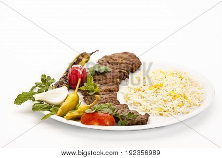Closeup on grilled lamb kebab with rice and herb served on a plain plate. Tender pieces of lamb fillet already taken off the skewer. Low angle view studio shot over white table top background.