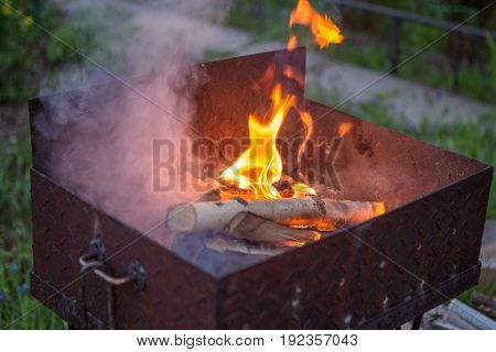 Photo of barbecue with burning log, smoke in street in summer