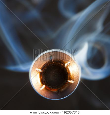 Bullet with a hollow point design and smoke coming at the viewer