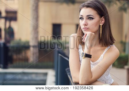 Horizontal portrait of young european model with bob cut hairstyle trendy make up with false eyelashes and in white crop top. Serious emotion