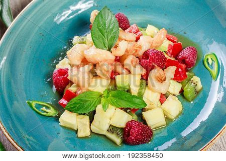 Fruit salad with shrimp avocado bulgarian pepper kiwi pineapple raspberries in plate on wooden background close up. Mediterranean food. Top view