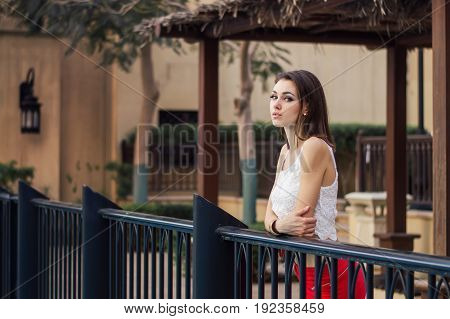 Young european female in white crop top and red skirt standing near metal fence. Sensual and elegant outfit. Bob cut hairstyle
