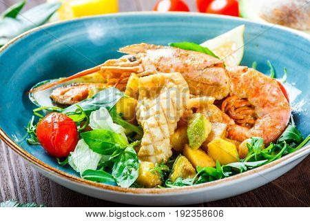 Warm salad with seafood langoustine mussels shrimps squid scallops mango pineapple avocado arugula and basil on wooden background close up. Mediterranean food. Top view