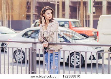Young european female with trendy bob cut hairstyle standing near busy road in city center. Female in beige jacket and blue jeans standing in Dubai downtown