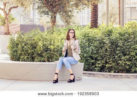 Female with stylish bob cut eye glasses beige jacket blue jeans and high heel shoes sitting in the park. Young european woman in casual clothes in Dubai downtown UAE. Big city life. Lifestyle concept