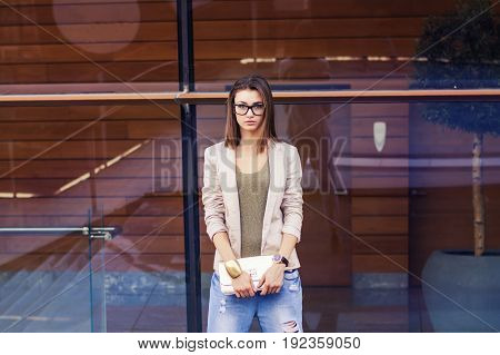 Youn european female model with eyeglasses bob cut hairstyle beige casual jacket blue jeans and golden clutch. Casual lifestyle concept