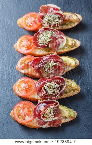 Appetizer bruschetta with prosciutto tomato zucchini on ciabatta bread on stone slate background close up. Delicious snacks sandwiches crostini antipasti on party or picnic time. Top view