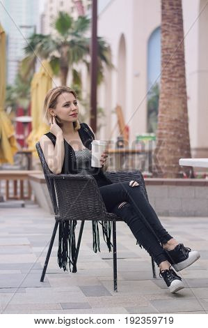Vertical photo of european female with short blond hair sitting outside with a cup of coffee