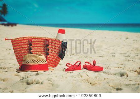 bag, suncream, glasses and flip flops on tropical beach