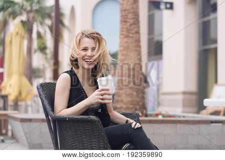 Young happy blond female having fun at open air terrace with a cup of coffee. Big city life. Happiness concept. Coffee drinking