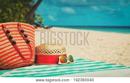 hat, sunglasses and bag on tropical beach
