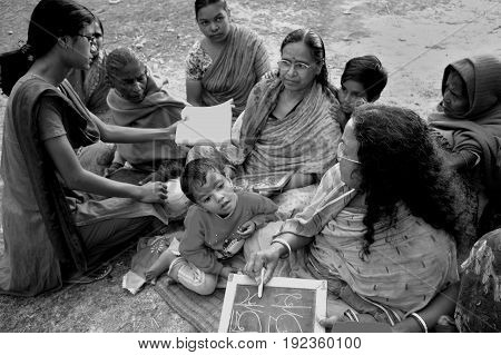KOLKATA, JANUARY 20, 2007: A young girl is helping an ender woman to understand the alphabets on January 20, 2007 in a rural area near Kolkata, India.